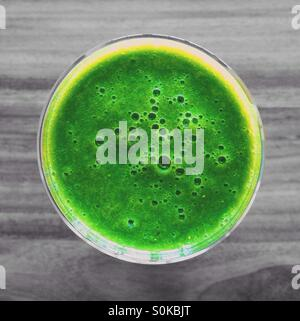 Colorful green smoothie on colorless grey background - Stock Photo