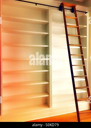 Empty bookshelves with  rolling ladder - Stock Photo