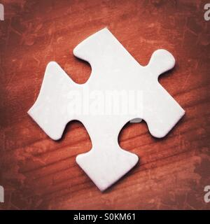 Blank white jigsaw puzzle piece on a wooden surface with grunge filter effects - Stock Photo