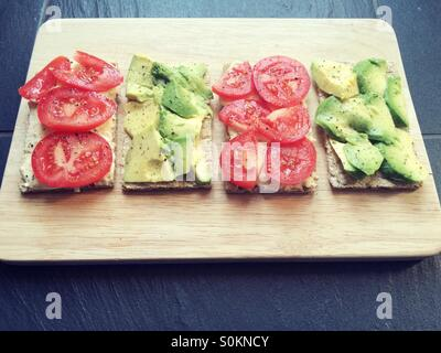 Tomatoes and avocado crackers with hummus on a wooden board - Stock Photo
