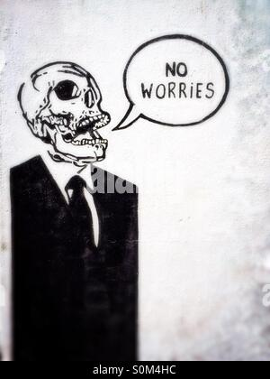 Street art of a human skeleton in suit with speech bubble containing the words No Worries, wall in Dublin, Ireland - Stock Photo