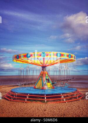 Carousel chair swing amusement ride at an out of season sunlit empty beach. Cleethorpes North East Lincolnshire, - Stock Photo