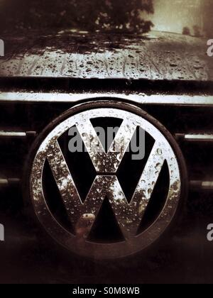 VW logo on the front of the car wet with rain - Stock Photo