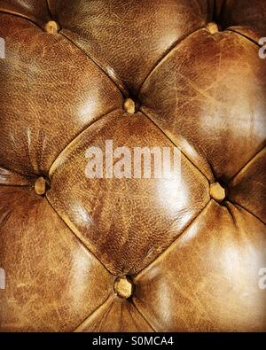 Close-up of a brown, leather Chesterfield seat. - Stock Photo
