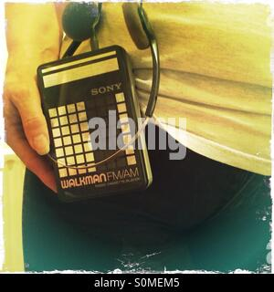 Woman holding Walkman radio cassette personal music player used in the days before iPods mp 3 players - Stock Photo