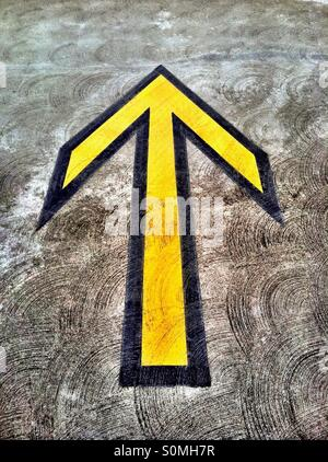 Yellow directional arrow on pavement in parking structure - Stock Photo