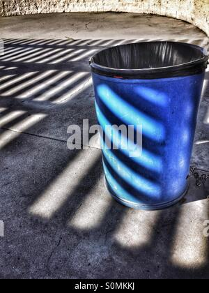 Afternoon Shadows, Lines, And Patterns Decorate A Blue Trash Can - Stock Photo
