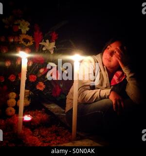A girl sits on a tomb during All Souls Day in Mexico City. The Day of the Dead celebration mixes Pre-Hispanic traditions - Stock Photo