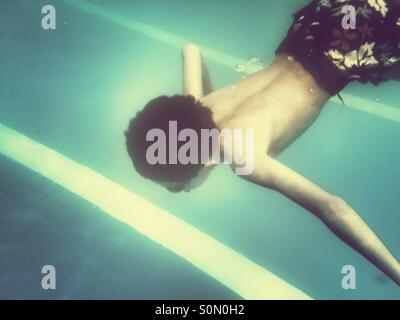 Bou swimming underwater in the pool - Stock Photo