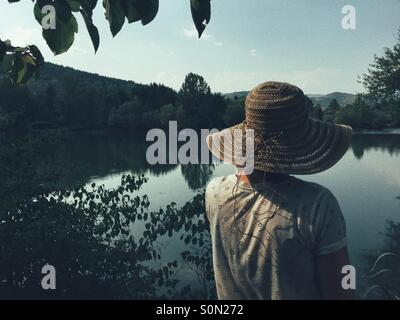Rear view of Woman looking across lake - Stock Photo