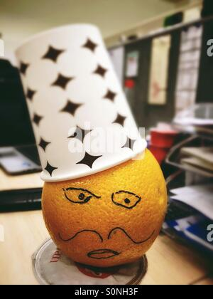 Office fun with an orange man wearing hat made by paper cup. - Stock Photo