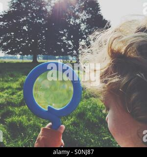 Boy looking for deer with a magnifying glass - Stock Photo