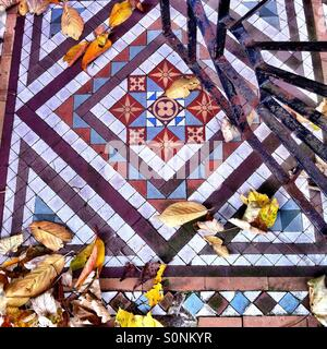 Fallen autumn leaves on coloured tiles at entrance of house - Stock Photo