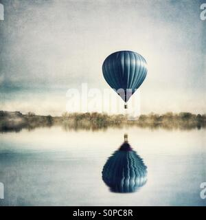 Reflection of hot air balloon in lake - Stock Photo