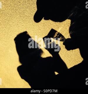 Shadow of a couple having a champagne toast - Stock Photo