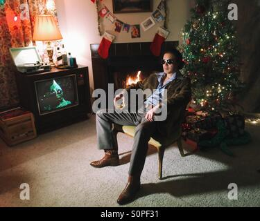 man in vintage clothes sits in front of Christmas tree near 1980-s TV set and fireplace - Stock Photo