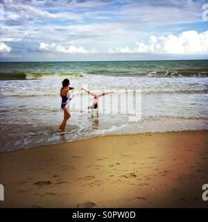 Woman taking a picture of a girl doing a cartwheel on a beach - Stock Photo