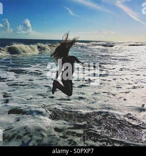 Girl jumping in the ocean waves - Stock Photo