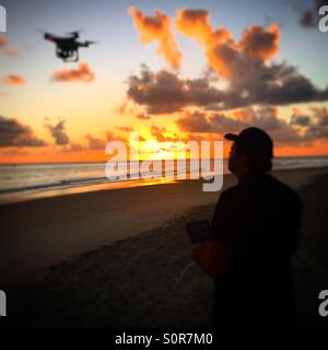 Drone pilot at a beautiful sunrise on background. - Stock Photo