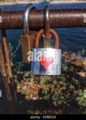 Lock with red heart on a bridge - Stock Photo
