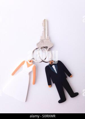 Two key rings in the shape of a bride and groom joined together with one key. - Stock Photo