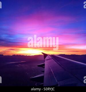 Beautiful sunrise at take off from Zurich, Switzerland, showing wing and mountains. - Stock Photo