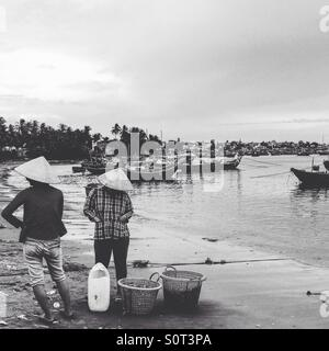 Fishing village Mui Ne Vietnam. Black and white image of local fisherwomen and bay scene - Stock Photo
