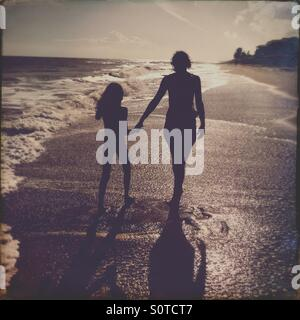 Mother and daughter walking on a Florida beach - Stock Photo