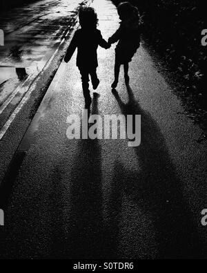 Silhouette of two children holding hands - Stock Photo