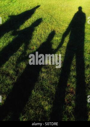 The Shadows of a Happy Family with hands joined whilst out on a winter walk in a field of green grass. Photo Credit - Stock Photo
