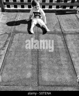 Boy sitting alone in the sun - Stock Photo