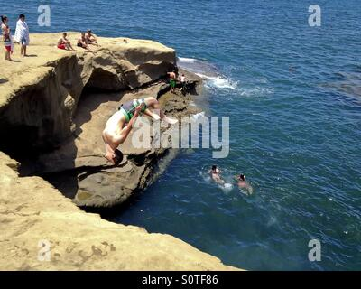 Young daring man doing a backflip off cliff into ocean, Sunset Cliffs, California, USA - Stock Photo