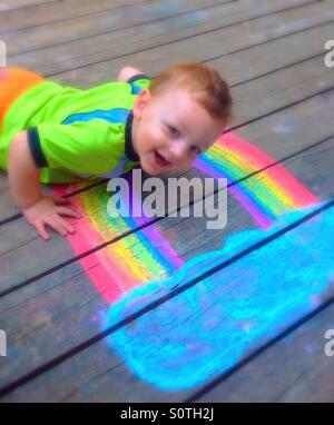 Laying on Mom's Chalk Rainbow :) - Stock Photo