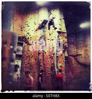 Pulling on plastic - Indoor rock climbing - Stock Photo