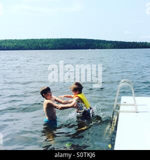 A ten year old boy catching his 5 year old brother who is jumping in the lake. The little brother is wearing a life - Stock Photo