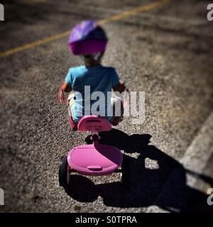 Little girl riding a tricycle in an empty parking lot - Stock Photo