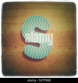 Textured foam letter S on a grungy wood background - Stock Photo
