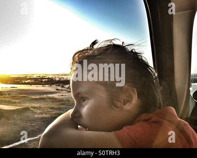 Boy looking out car window - Stock Photo