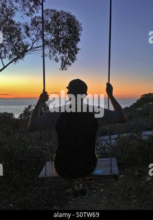 Silhouette of a man on a swing set during colorful sunset, La Jolla, California, USA - Stock Photo