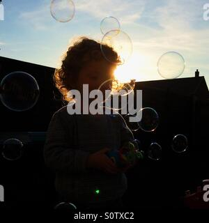 Silhouetted child playing with bubbles in garden - Stock Photo