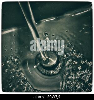 Water running down the drain in bathroom sink - Stock Photo