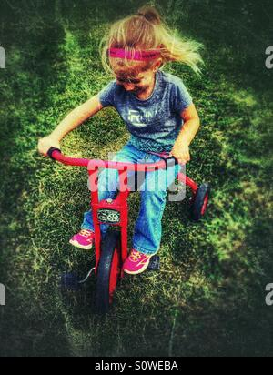 Girl riding a vintage Locomotion tricycle in the grass - Stock Photo