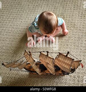 Baby reaching for a model ship sitting on the floor - Stock Photo