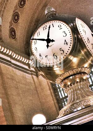 The four sided ornate clock dominates the concourse at Grand Central terminal, NYC - Stock Photo