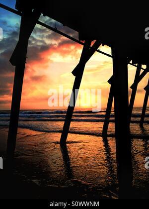 Beautiful sunrise under a pier in Myrtle Beach South Carolina - Stock Photo