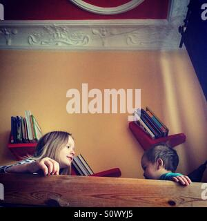 Siblings sitting on a top bunk bed in the morning - Stock Photo