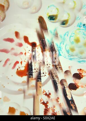 Kaleidoscopic image of brushes on white palettes with paint - Stock Photo