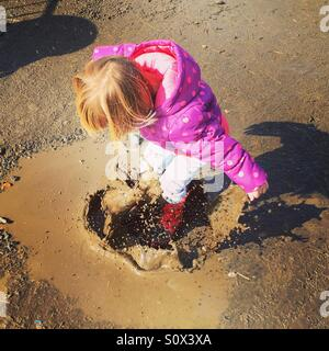 Girl toddler jumping up and down in muddy puddles - Stock Photo
