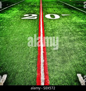 Twenty yard line painted red on an American football field - Stock Photo