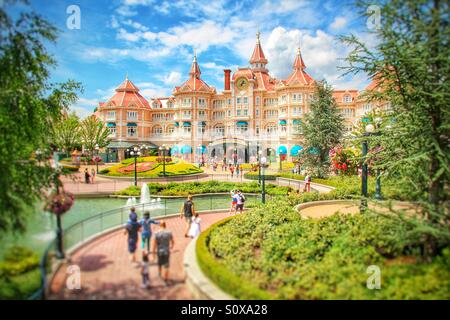 The Disneyland Hotel in Paris with tourists in the foreground under a beautiful blue sky. - Stock Photo
